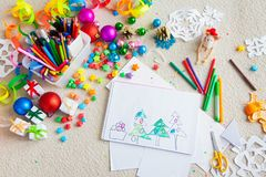 The child draws a Christmas tree with markers and colored pencil. A boy draws a Christmas tree. Child`s drawing Christmas. The child lies on the floor and draws Stock Images