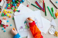 The child draws a Christmas tree with markers and colored pencil. A boy draws a Christmas tree. Child`s drawing Christmas. The child lies on the floor and draws Stock Photo