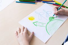 The child draws with colored pencils a green house, an electric car and a windy power station. Concept of ecology stock photo