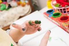 Child draws a colorful finger paints. On white paper Stock Images