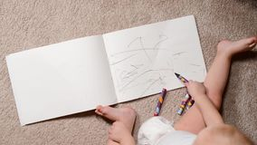 Child draws with crayons in an album. Top view stock footage
