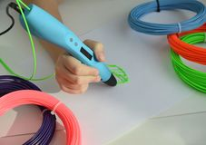 Child draws a 3D pen green leaf. Girl draws with a 3d pen. The hands of the child hold the 3d blue pen and draws a green leaf with plastic stock images