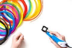 Child draws 3Dpen. Colorful rainbow plastic filaments for 3D pen laying on white. New toy for child. Child draws 3Dpen. Colorful rainbow plastic filaments with Royalty Free Stock Image