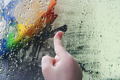 The child, draws a finger on glass. Through which the multi-coloured wall is visible Stock Photo