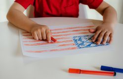 The child draws the flag of America. stock image