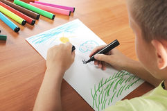 Child draws green grass and sun on paper Royalty Free Stock Photos