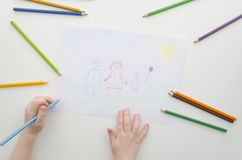 A child draws his family with pencils. Child`s drawing and colored pencils. Family drawing on a white paper. Top view stock images