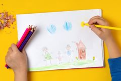 The child draws his family on a piece of paper with colored pencils. My happy family. The concept of child psychology. The child draws his family on a piece of royalty free stock photo