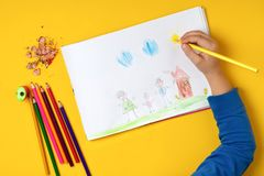 The child draws his family on a piece of paper with colored pencils. My happy family. The concept of child psychology. The child draws his family on a piece of royalty free stock image