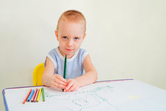 Child draws. Little boy at a desk learning to draw with markers and pencils. Child with a felt-tip pen. Photo with limited depth of field Royalty Free Stock Photography