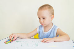 Child draws. Little boy at a desk learning to draw with pencils. Child chooses a pencil Royalty Free Stock Images