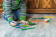 Child draws with markers and pencils drawing. On the floor stock images
