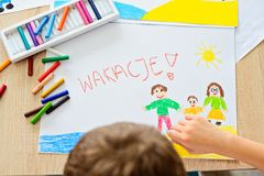 Child draws oil pastel drawing of family on the beach. Wakacje - Polish word for summer vacation royalty free stock images