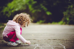 Child Draws On Asphalt In The Park. Royalty Free Stock Photography