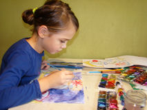 Child draws paints. Girl draws a picture paints while sitting at table Stock Image