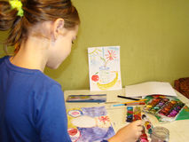 Child draws paints. Girl draws a picture paints while sitting at table Royalty Free Stock Photos
