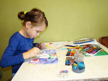 Child draws paints. Girl draws a picture paints while sitting at table Royalty Free Stock Photography