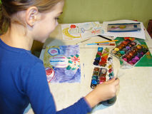 Child draws paints. Girl draws a picture paints while sitting at table Stock Images
