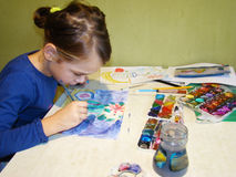 Child draws paints. Girl draws a picture paints while sitting at table Royalty Free Stock Image