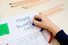 Child draws a pastel drawing of his teacher in school class. Little child draws a pastel drawing of his teacher in school class. Teachers day royalty free stock image