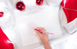 Beautiful creative Christmas background with pattern. The child draws Santa Claus with a red pen on a white sheet and red