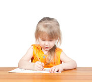 The child draws at the table. Stock Photos
