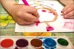 Child draws a tree with flowers. Children's hand draws pink flowers on a tree Stock Image