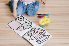 Child draws water colors in coloring book. On parquet floor stock photo