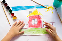 The child draws in watercolor. The child draws watercolor on paper stock image