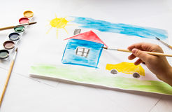 The child draws in watercolor. The child draws watercolor on paper stock photography