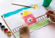 The child draws in watercolor. The child draws watercolor on paper stock images