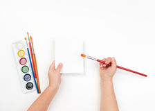 Child draws watercolors on blank sheet Stock Images