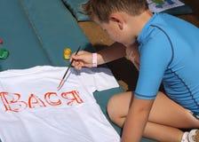 Child draws on a white T-shirt Royalty Free Stock Photo