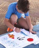 Child draws on a white T-shirt. Child in a blue T-shirt draws on a white shirt on the sand Royalty Free Stock Photography