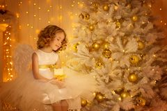 Child Dream under Christmas Tree, Happy Girl with Candle. Sitting in Fantasy Night Decorated Room royalty free stock photos