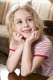 Child dreams. Smiling blond girl in stripe t-shirt sitting at the coffee table Royalty Free Stock Photo