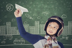 Child dreams of becoming an aviator. Little boy wearing helmet and dreams of becoming an aviator while playing a paper plane Royalty Free Stock Images