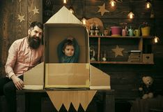 Child dreams. Rocket launch concept. Kid happy sit in cardboard hand made rocket. Boy play with dad, father, little. Cosmonaut sit in rocket made out of stock photography