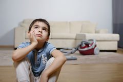 A child dreming and not willing to do the cleaning. A boy not willing to do the homework Royalty Free Stock Photo