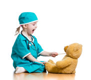 Child dressed as doctor playing with toy. Adorable child dressed as doctor playing with toy over white