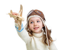Child dressed as pilot and playing with wooden airplane toy isol Stock Photo