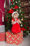 Child dressed as Santa in box with gift bag Royalty Free Stock Photos