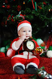 Child dressed as Santa Claus gnawing teeth clock alarm . Ch Stock Images