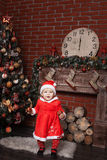 Child dressed as Santa Claus near the Christmas tree. Baby girl dressed as Santa Claus stands near a Christmas tree and holding Christmas balls Royalty Free Stock Images