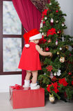Child dressed as Santa decorates Christmas tree Royalty Free Stock Image