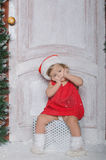 Child dressed as Santa is sitting on gifts Stock Photos