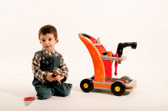 Child dressed as a worker with cart tools Stock Photo