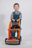 Child dressed as a worker with cart tools Royalty Free Stock Photos