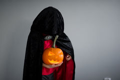 Child is dressed in black -red toga with hood. It is a costume for Halloween. He represents the mysterious wizard. The hood covers the face. Child holds Stock Images