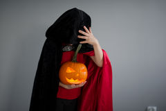 Child is dressed in black - red toga with hood. Child is dressed in black -red toga with hood. It is a costume for Halloween. He represents the mysterious Stock Images
